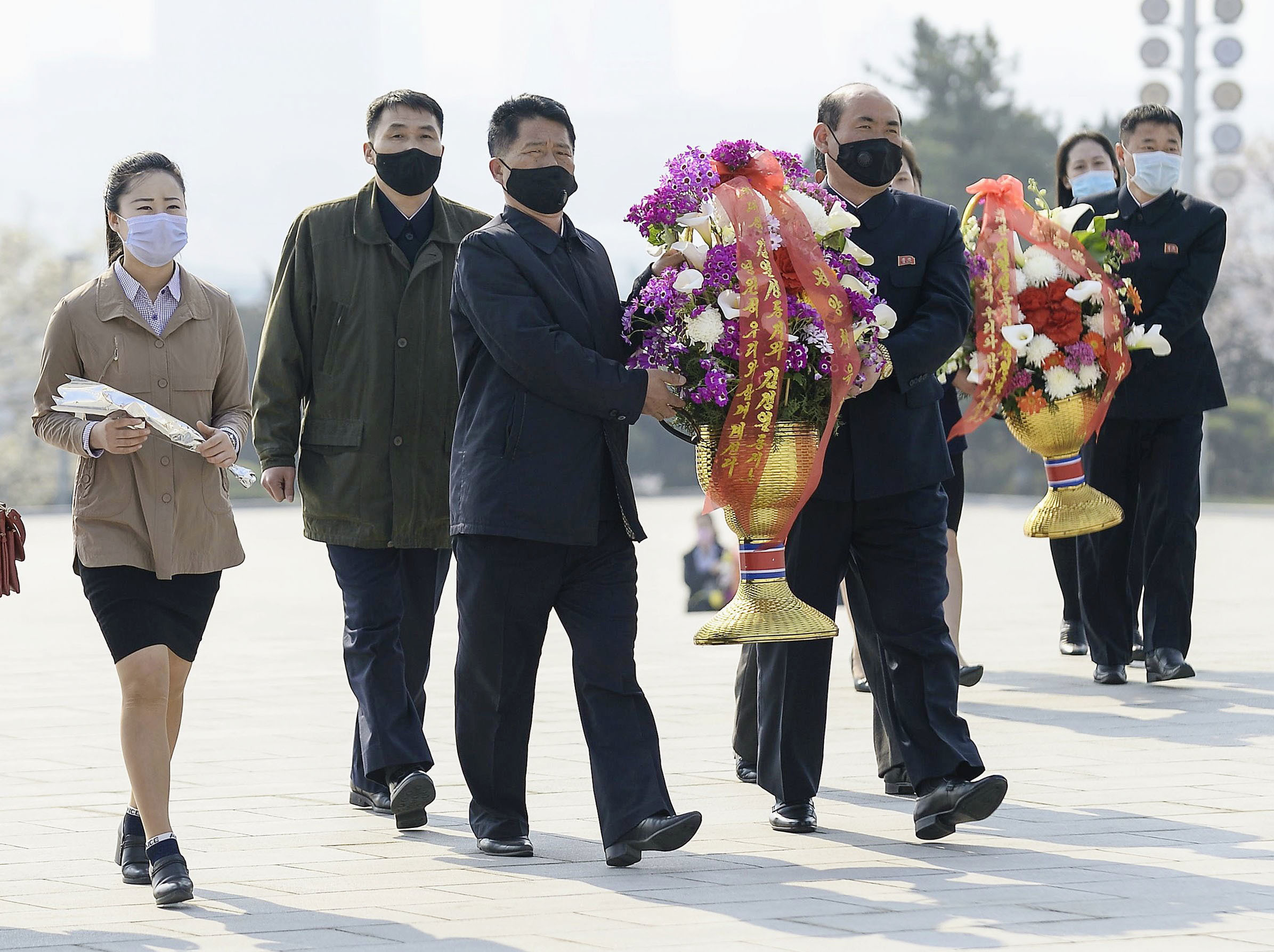 North Koreans wearing masks visit offer flowers on the 108th anniversary of the birth Kim Il Sung. Source: AAP