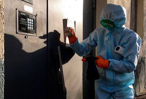 A communal worker sprays disinfectant on the door of a residential building in Moscow.