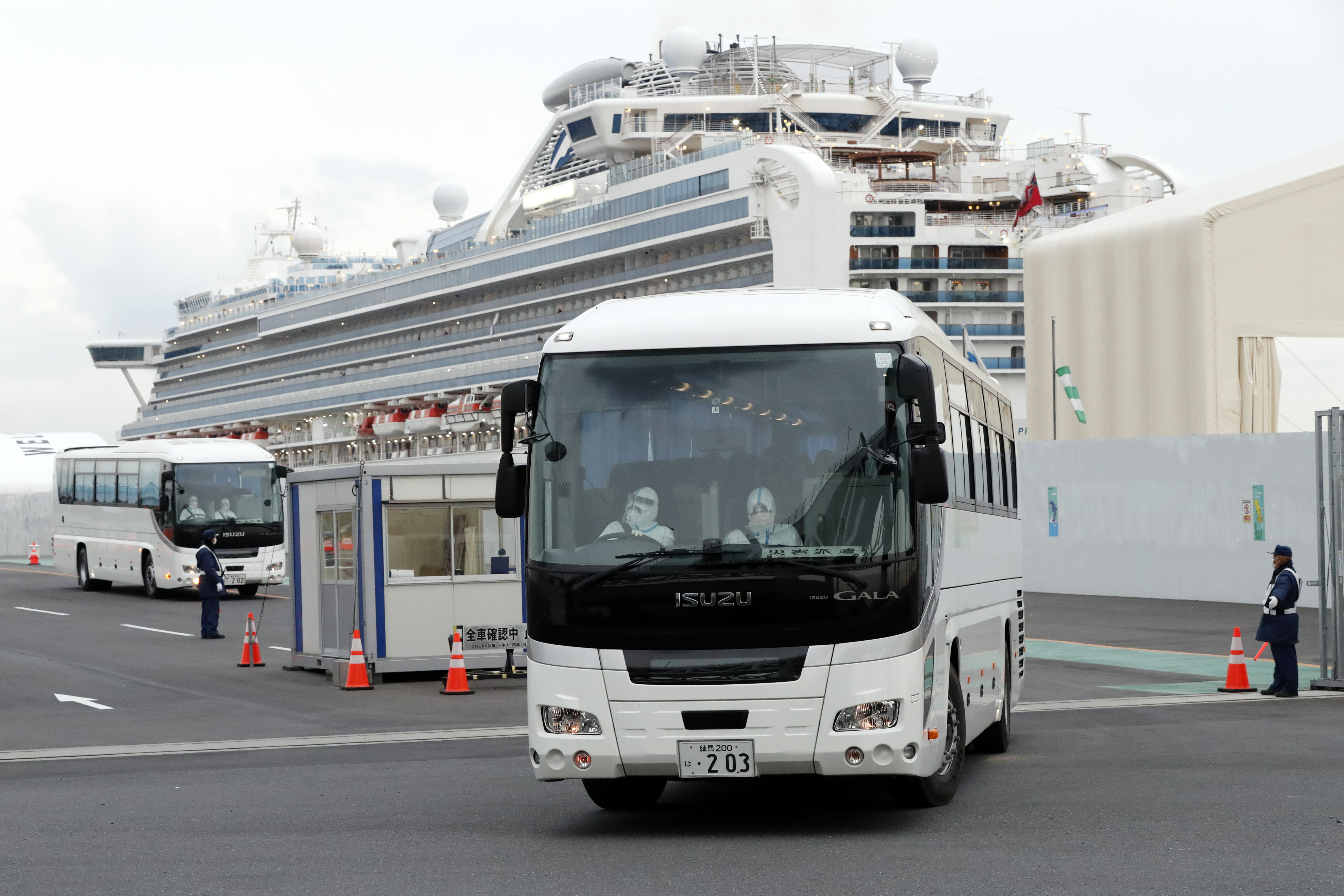 Bus carrying the passengers from the quarantined Diamond Princess cruise ship leave a port in Yokohama, near Tokyo, Thursday, Feb. 20, 2020. Passengers tested negative for COVID-19 started disembarking since Wednesday. (Eugene Hoshiko/AP)