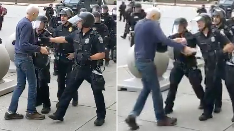 An elderly man walks up to police in full riot gear, two police officers push the man back and he falls backward hitting his head on the concrete.