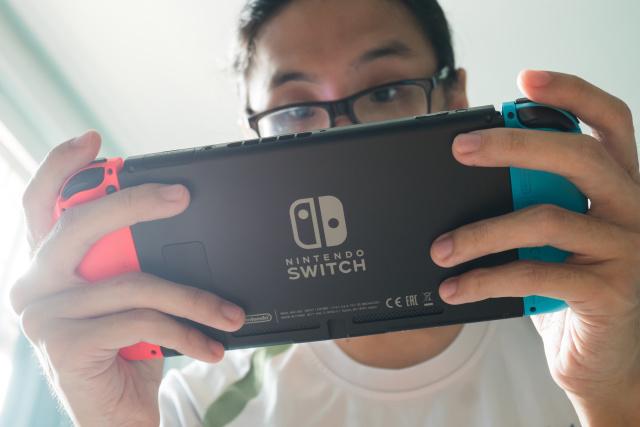 Bangkok, Thailand - October 31, 2017 : A man playing Nintendo Switch.
