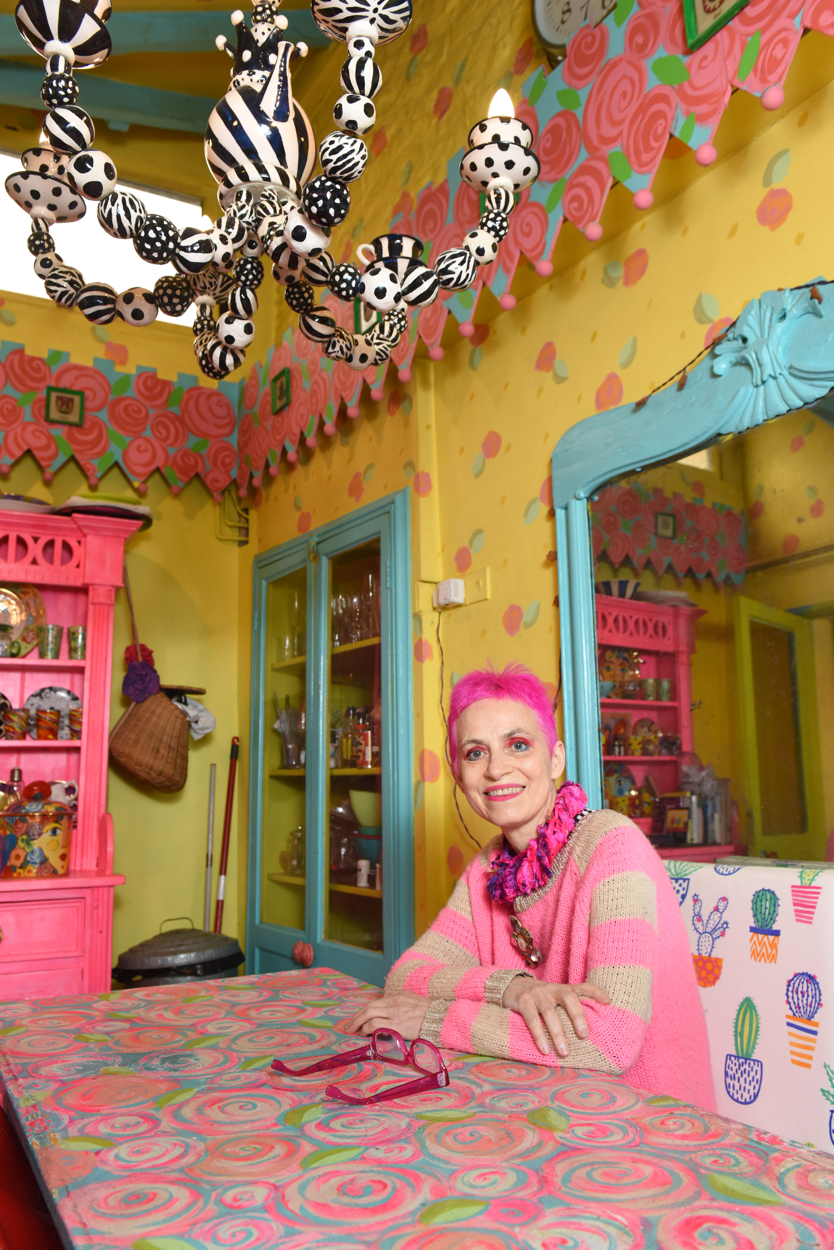 PIC BY MERCURY PRESS (PICTURED Potter, Mary Rose Young, 61 has made her £500,000 home unsellable with her eccentric, colourful decor) A woman who spent more than 30 years turning her rundown cottage into a life-size doll house says her colourful decoration has made the house - which should be worth upwards of half a million pounds - unsellable.  Potter, Mary Rose Young, 61, has been painting the beautiful country cottage in leafy Lydney, Gloucs in her electric style by hand since 1987, when she bought the former squatter's house for just £30,000. After 27 years in the house, she put it on the market in 2014, where estate agents said the property should have been expected to fetch at least £500,000. But despite hoping to sell the property to open a B&B nearby, estate agents could only persuade one person to view the house - leaving the family stuck there. SEE MERCURY COPY