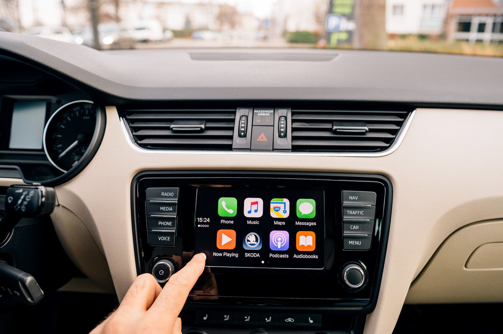 PARIS, FRANCE - DEC 13, 2016: Man pressing home button on the Apple CarPlay main screen in modern car dashboard. CarPlay is an Apple standard that enables a car radio or head unit to be a display and controller for an iPhone. It is available on all iPhone 5 and later with at least iOS 7.1.