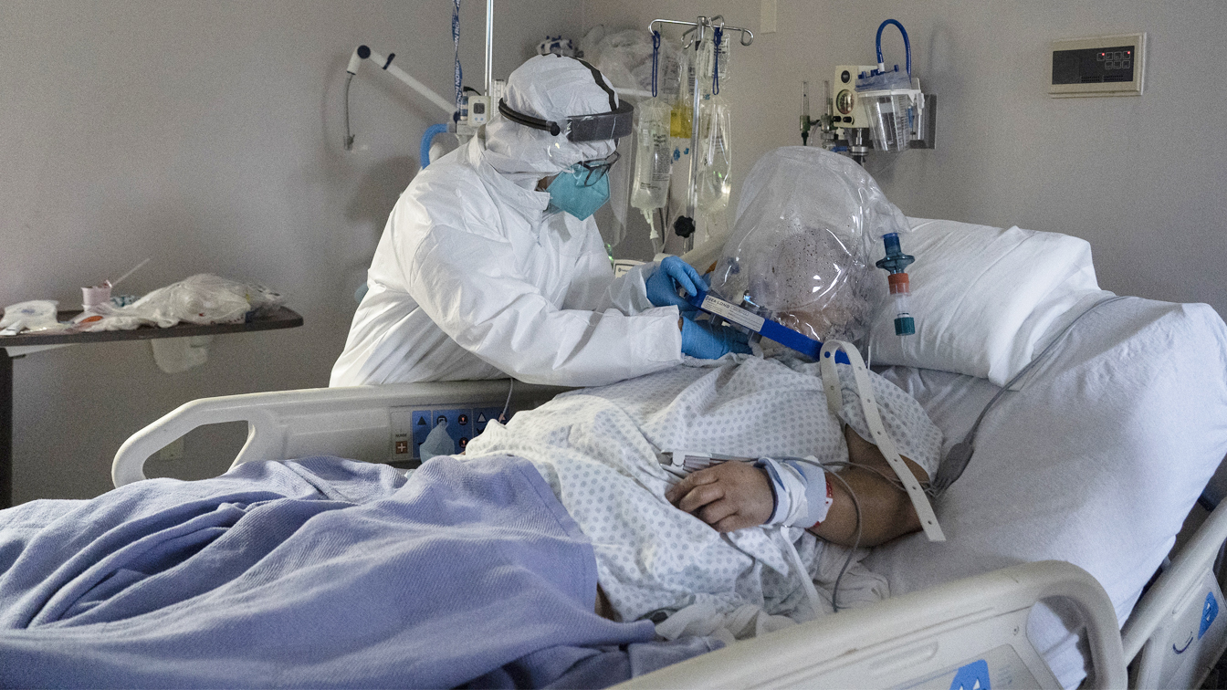 A member of the medical staff treats a patient who is wearing helmet-based ventilator in the COVID-19 intensive care unit at the United Memorial Medical Center on July 28, 2020 in Houston, Texas. (Go Nakamura/Getty Images)