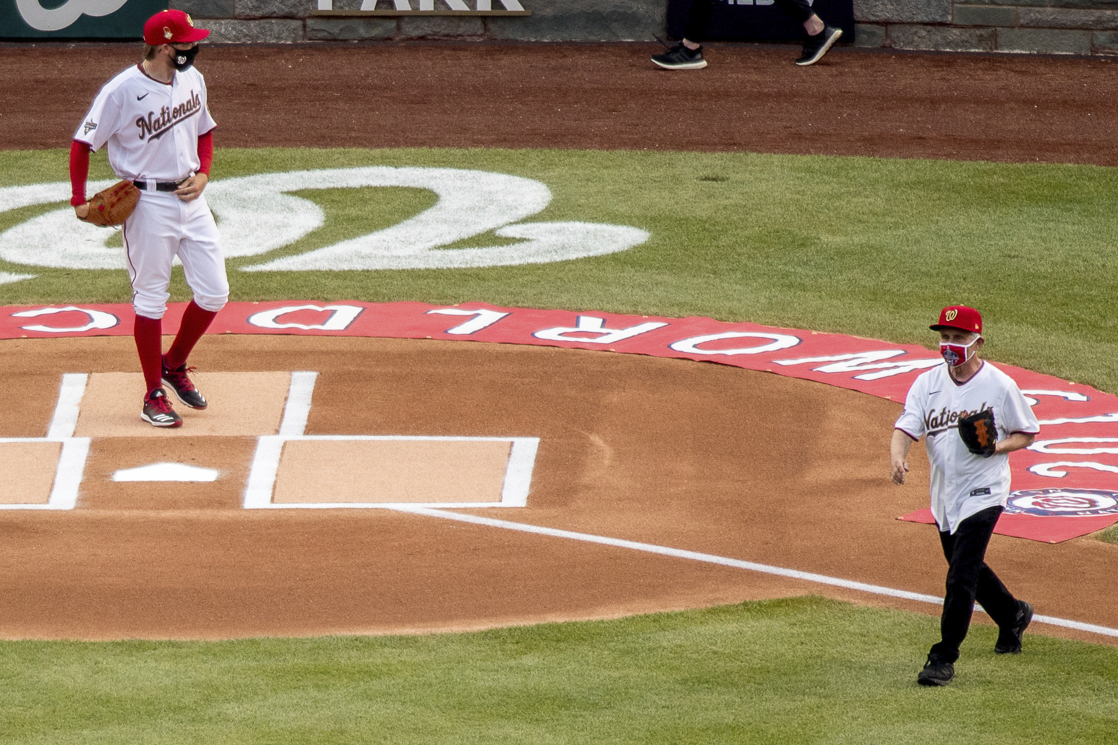 Dr. Anthony Fauci walks to the mound in Nationals gear while Sean Doolittle awaits at the plate.