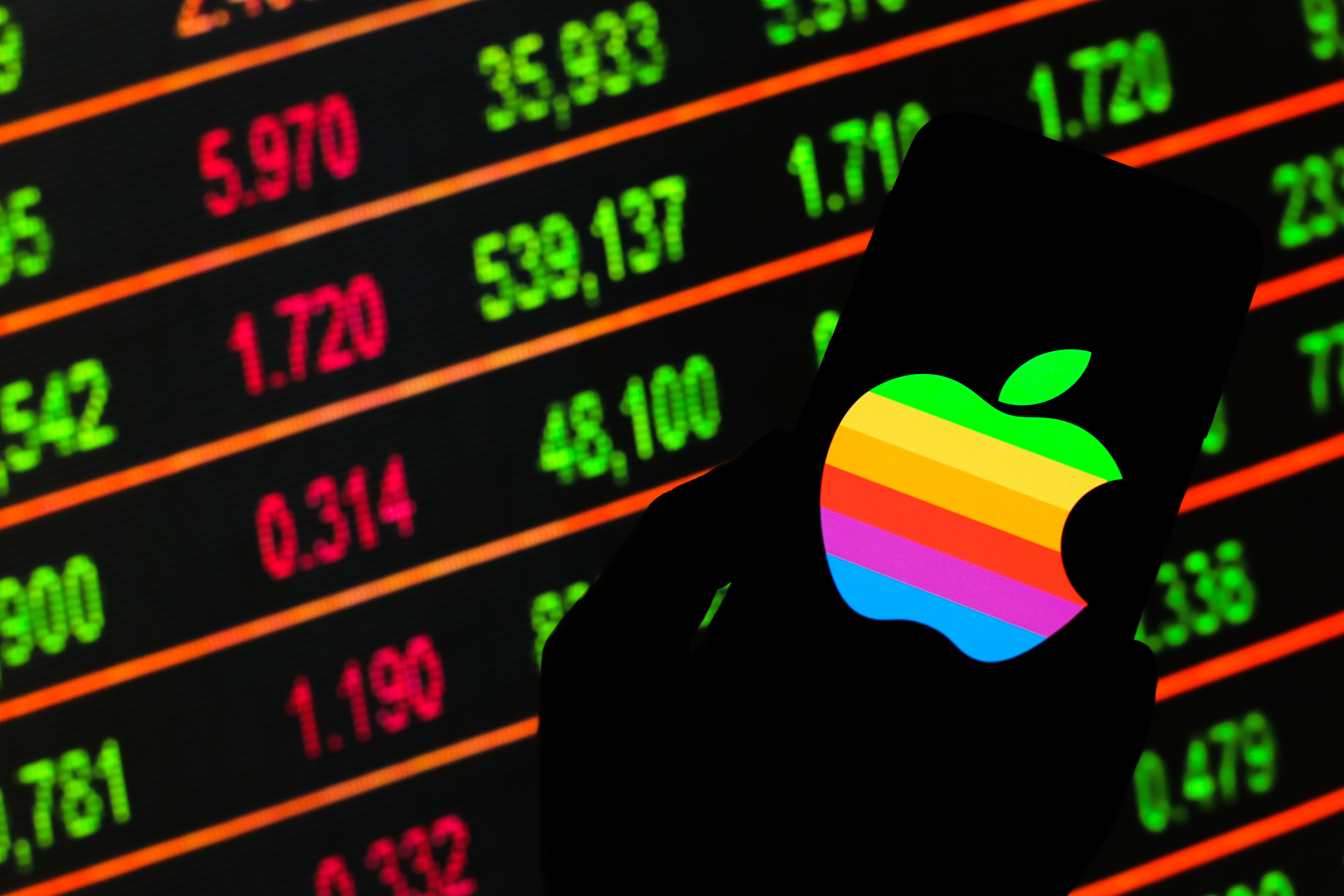 POLAND - 2020/03/13: In this photo illustration an Apple logo seen displayed on a smartphone. Stock market prices in the background as stock markets tumble all over the world. (Photo by Filip Radwanski/SOPA Images/LightRocket via Getty Images)