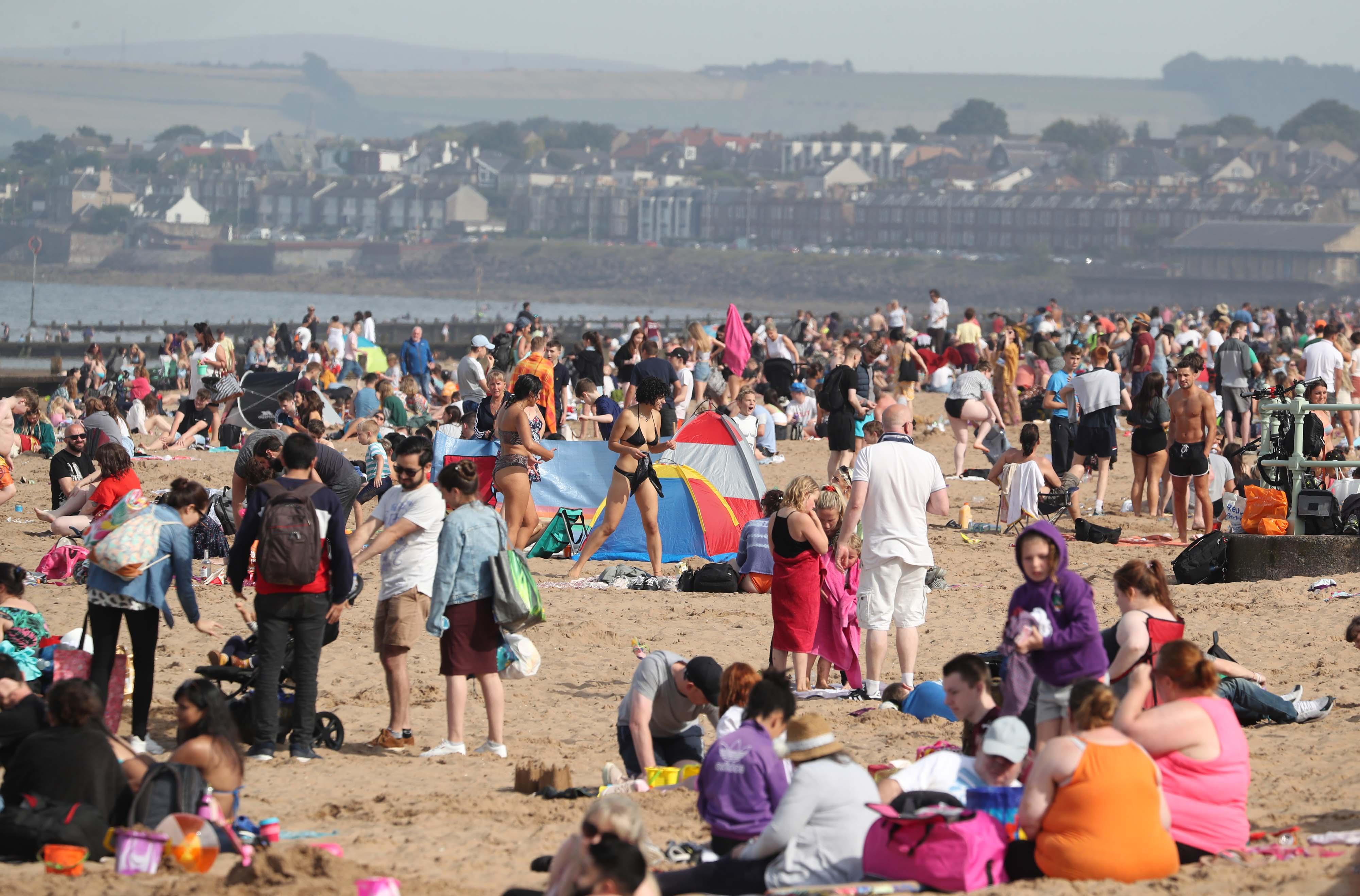 People enjoying the weather on Portobello Beach in Edinburgh.