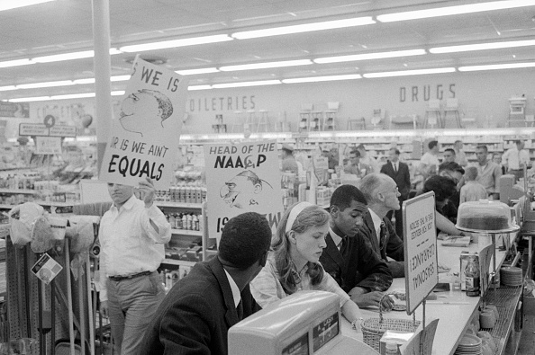 Demonstrators staging a sit-in at a drug store lunch counter in Arlington, VA, are picketed by American Nazi Party (George Lincoln Rockwell's group) members. The sit-in people were trying to break down racial barriers at the drug store lunch counter. (Photo by Wally McNamee/CORBIS/Corbis via Getty Images)