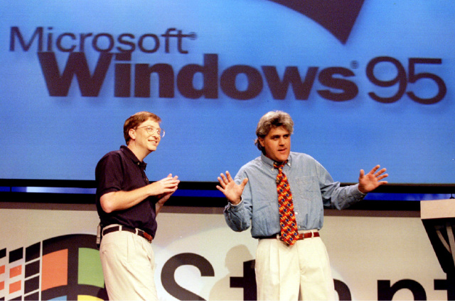Microsoft Chairman Bill Gates (L) looks on  as The Tonight Show's Jay Leno co-hosts the official launch of Windows '95 at the Microsoft campus in Redmond, Washington August 24 - PBEAHUNDADM