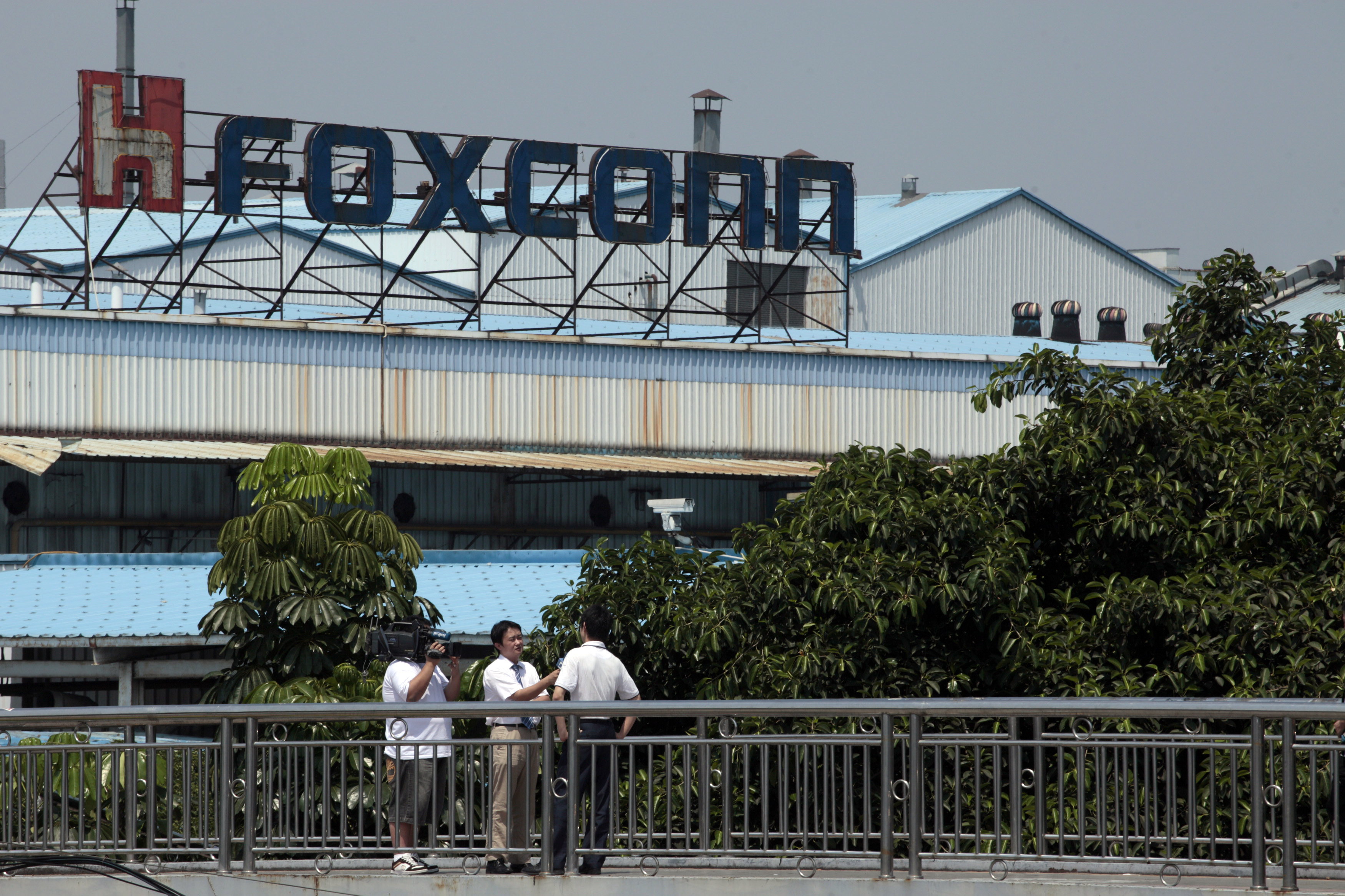 Employees of Foxconn speak to reporters outside one of the tech firm's factories in the southern Chinese city of Shenzhen May 25, 2010. An employee of Foxconn died early on Tuesday after falling from a building in southern city of Shenzhen, state media reported, the ninth such death at the firm's manufacturing hub this year. REUTERS/Tyrone Siu (CHINA - Tags: BUSINESS EMPLOYMENT SCI TECH DISASTER)