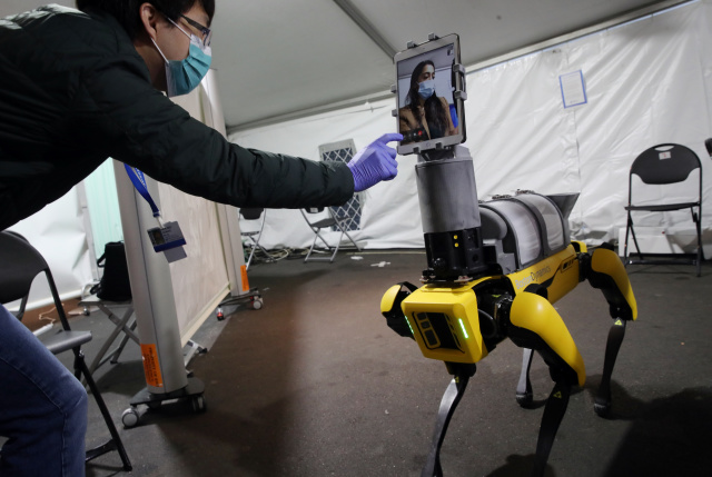 BOSTON, MA - APRIL 23: Research Scientist Hen-Wei Huang, left, talks about Spot the Robot, during a demonstration at Brigham And Women's Hospital in Boston on April 22, 2020. The demonstration featured a new mobile telemedicine platform, Spot the Robot, designed in collaboration with Brigham researchers. Spot, a Boston Dynamics robot, reduces health care worker exposure to potential Covid-19 patients and helps conserve the use of PPE. The demonstration included the robots iPad feature which visually links a patient looking at the robot with a clinician who may be steps away for easy and safe communication. Spot the Robot is currently in clinical use in the Brighams Emergency Department. (Photo by Craig F. Walker/The Boston Globe via Getty Images)