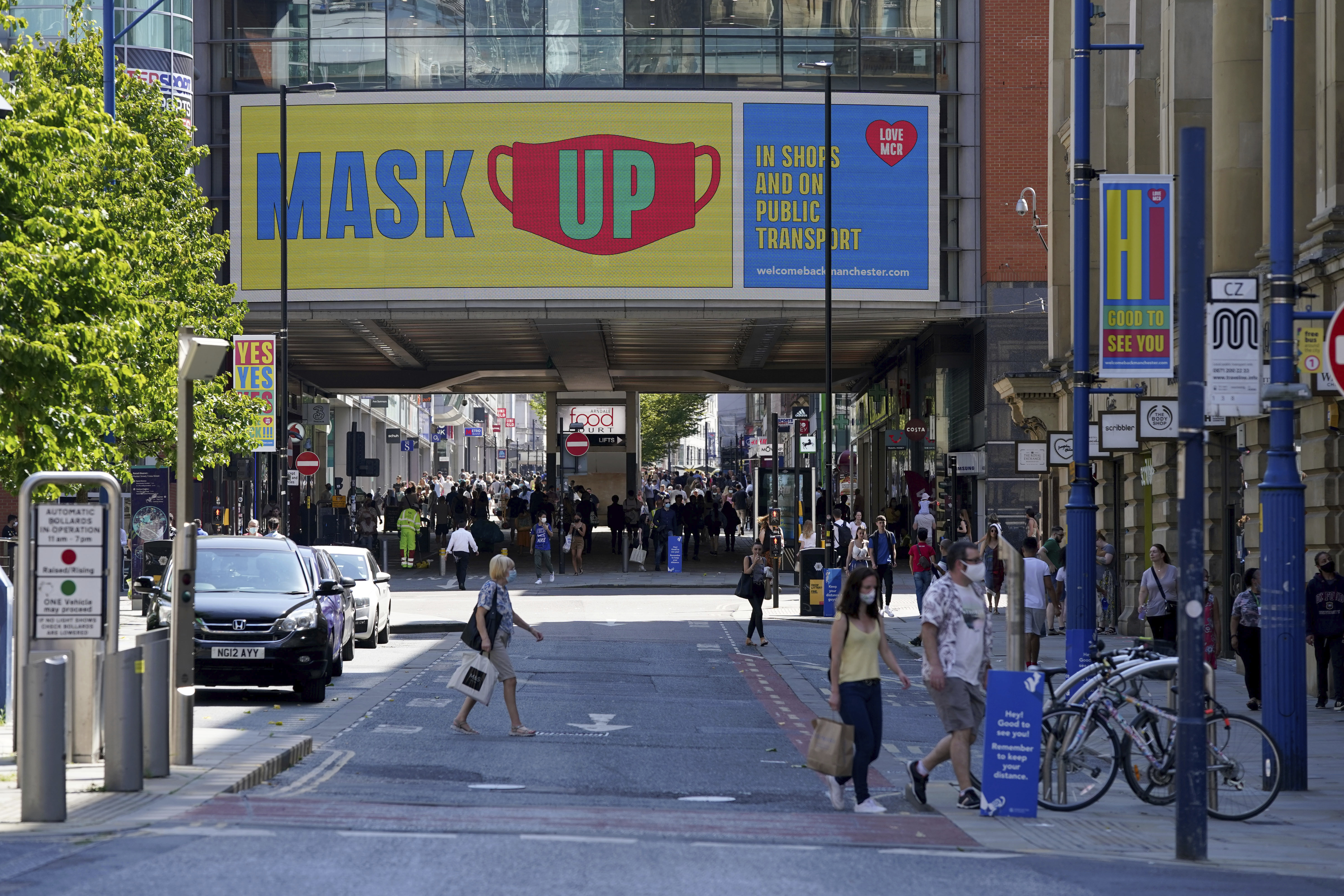 """People wearing face masks to try to stop the spread of coronavirus walk backdropped by a """"Mask Up"""" sign in Manchester, northern England, Friday, July 31, 2020. The British government on Thursday night announced new rules on gatherings in some parts of Northern England, including Manchester, that people there should not mix with other households in private homes or gardens in response to an increase trend in the number of cases of coronavirus cases per 100,000 people. (AP Photo/Jon Super)"""