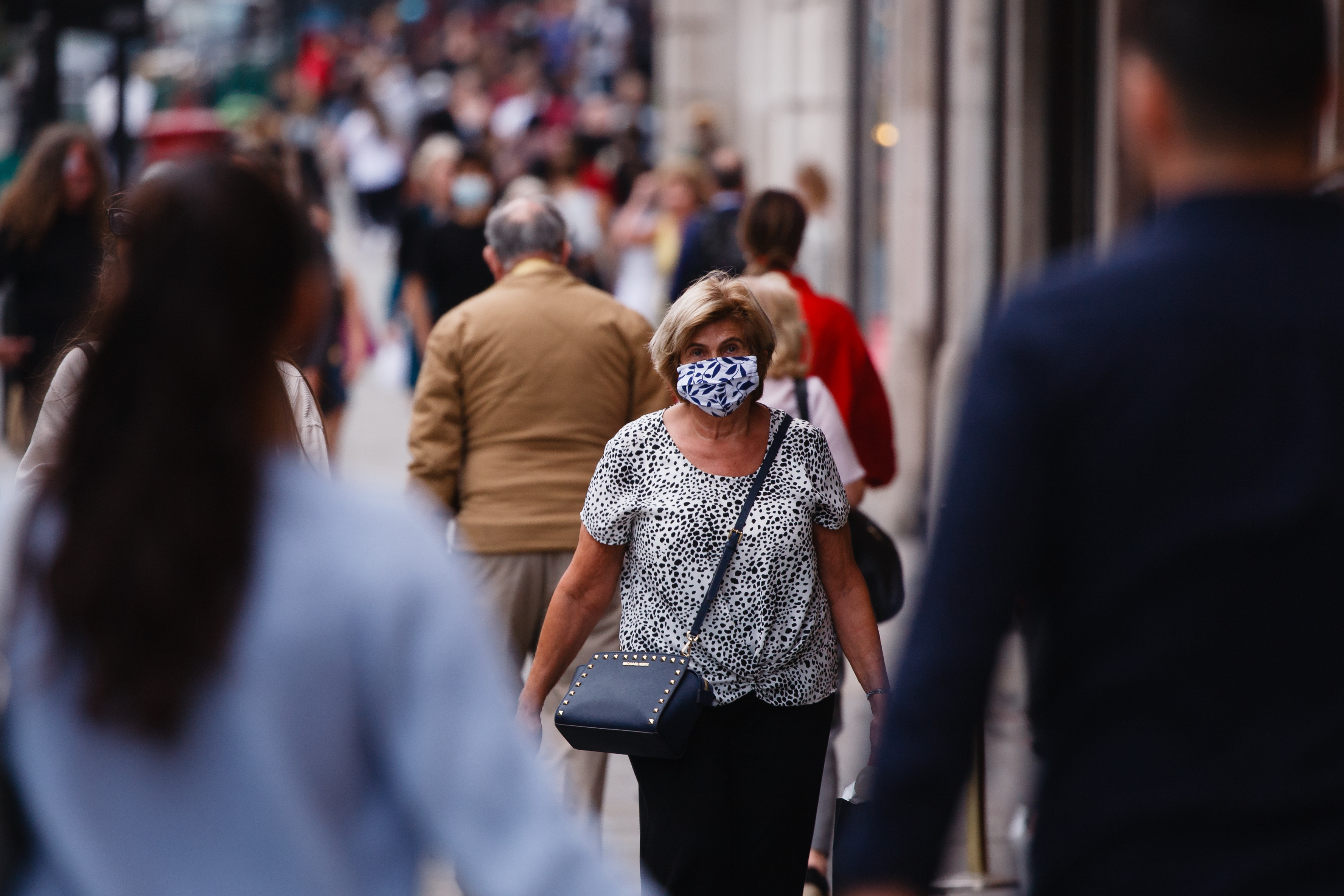 A woman wearing a face mask walks along Regent Street in London, England, on September 22, 2020. British Prime Minister Boris Johnson this afternoon announced a raft of new coronavirus restrictions to apply across England, possibly to last the next six months, including requiring pubs and restaurants to close at 10pm and for retail staff to all wear face masks. A return to home working where possible is also being encouraged. The new measures come amid fears of a 'second wave' of covid-19 deaths prompted by rising numbers of people testing positive in recent weeks. (Photo by David Cliff/NurPhoto via Getty Images)