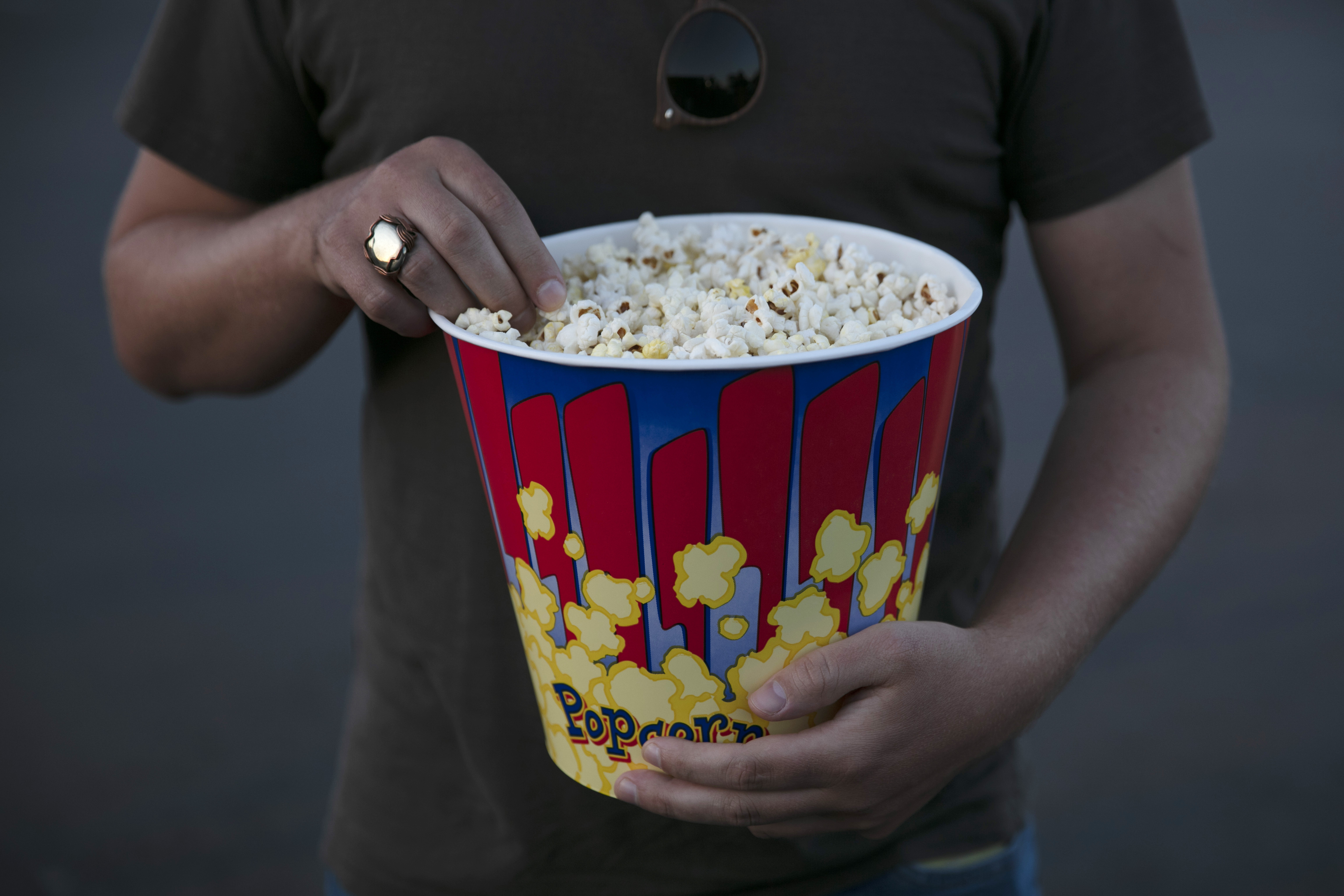 A moviegoer eats popcorn at Mission Tiki drive-in theater in Montclair, Calif., Thursday, May 28, 2020. California moved to further relax its coronavirus restrictions and help the battered economy. Flea markets, swap meets and drive-in movie theaters can resume operations. (AP Photo/Jae C. Hong)