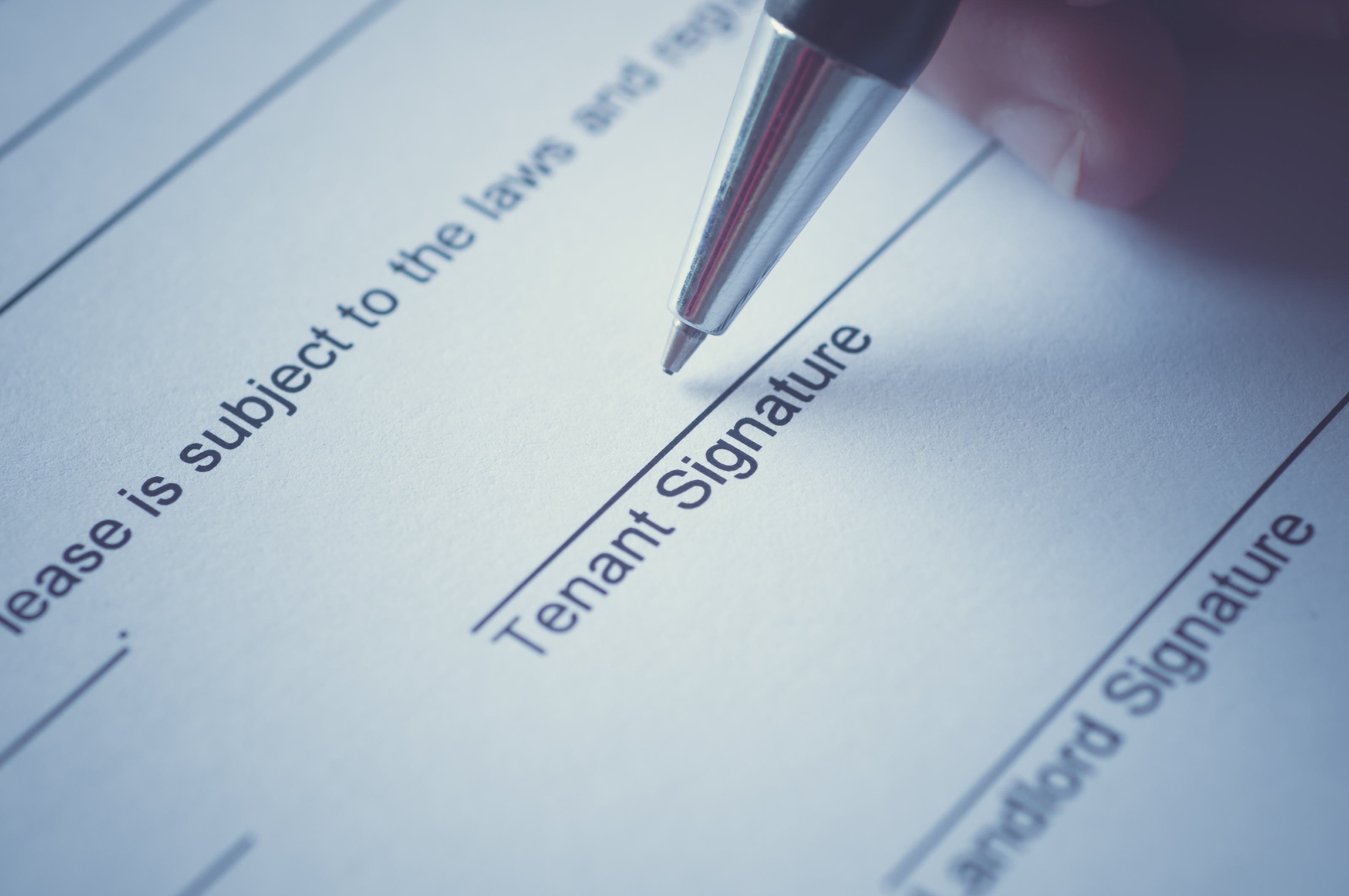 Rental agreement form with signing hand and pen.