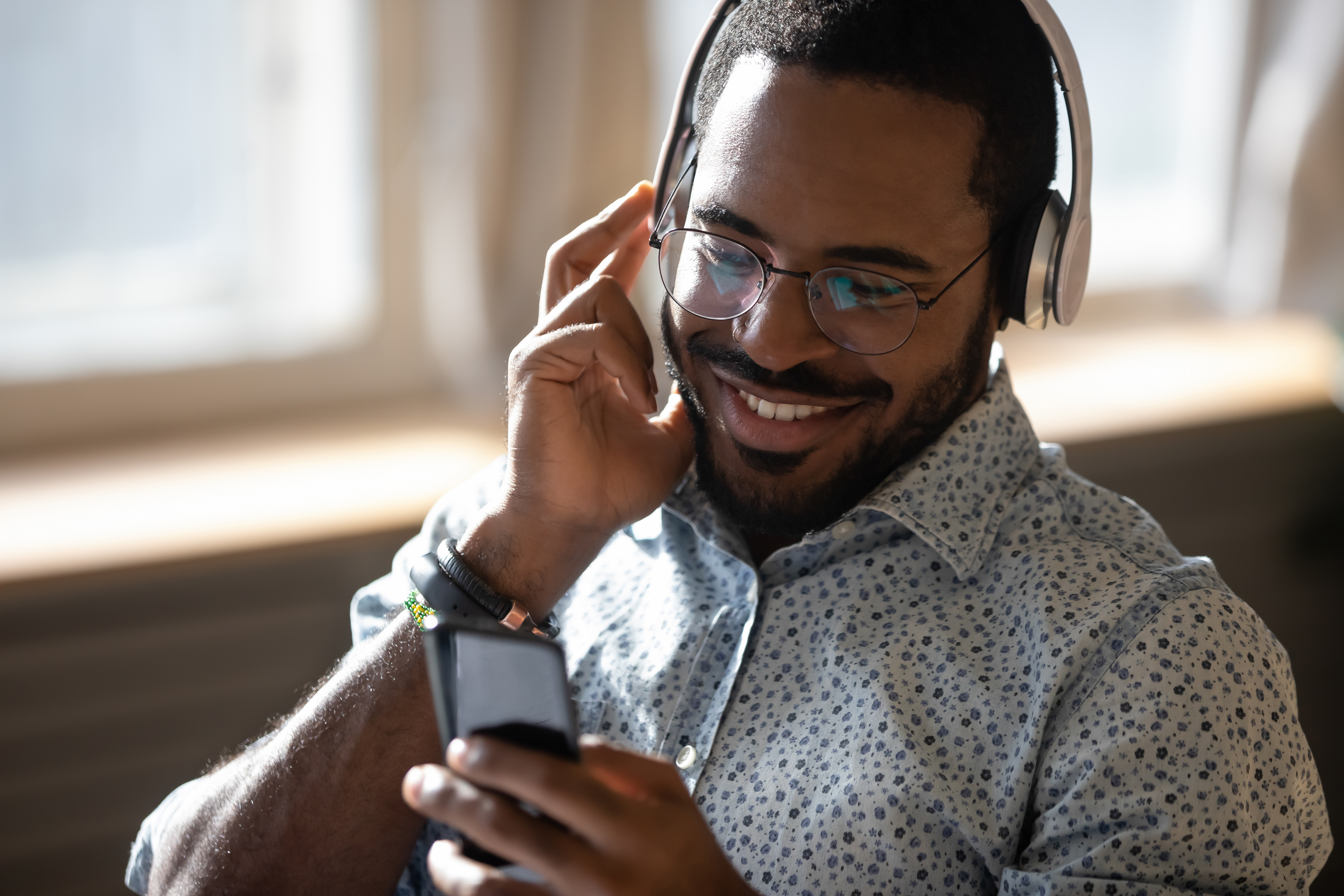 Smiling young adult african man wearing wireless headphones listening mobile music on smartphone, happy afro american guy using online player podcast audio book in app on cell phone relaxing at home