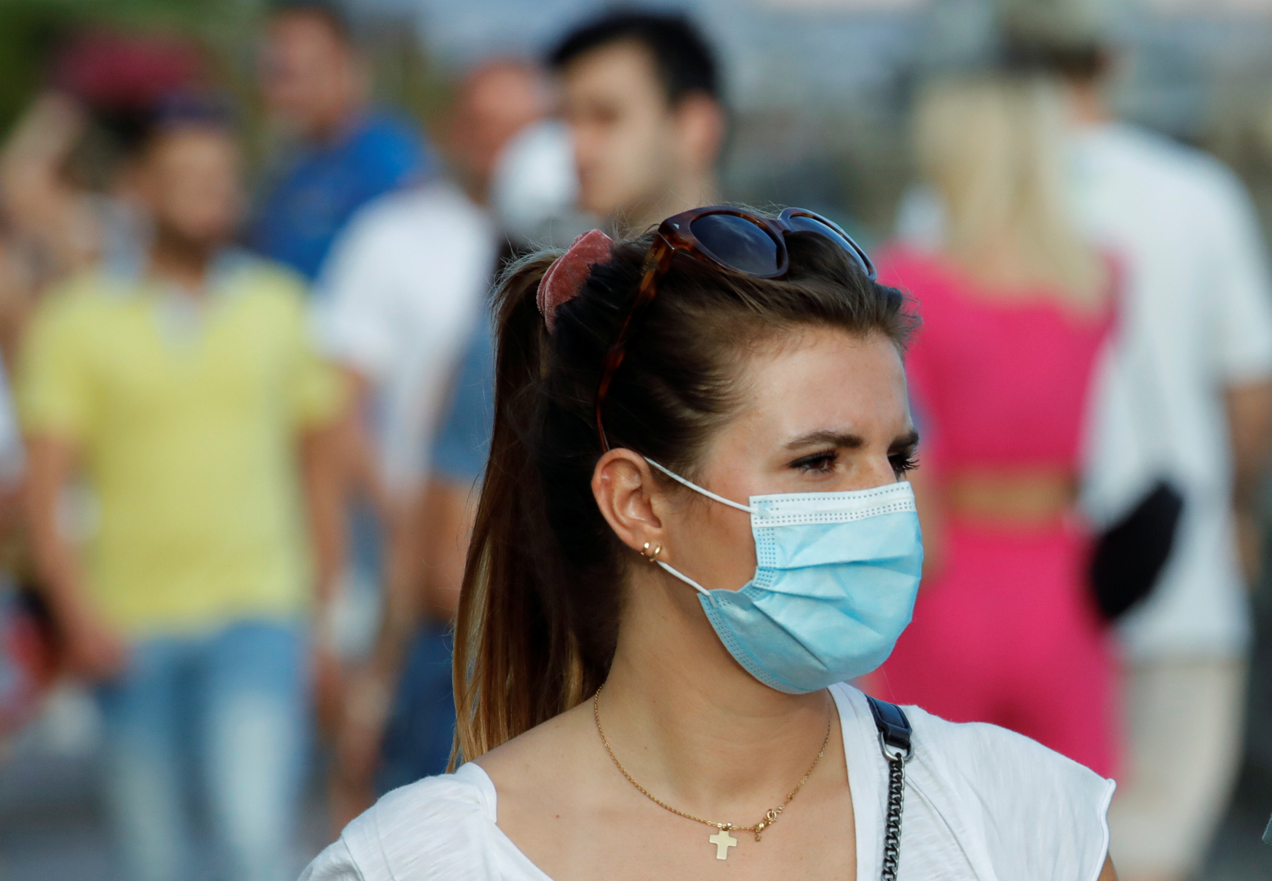 A woman wears a mask as she walks on the street following a government decree that face coverings must be worn between 6 p.m. and 6 a.m. in areas close to bars and pubs and where gatherings are more likely, due to the coronavirus disease (COVID-19) outbreak, in Naples, Italy August 17, 2020. REUTERS/Ciro De Luca