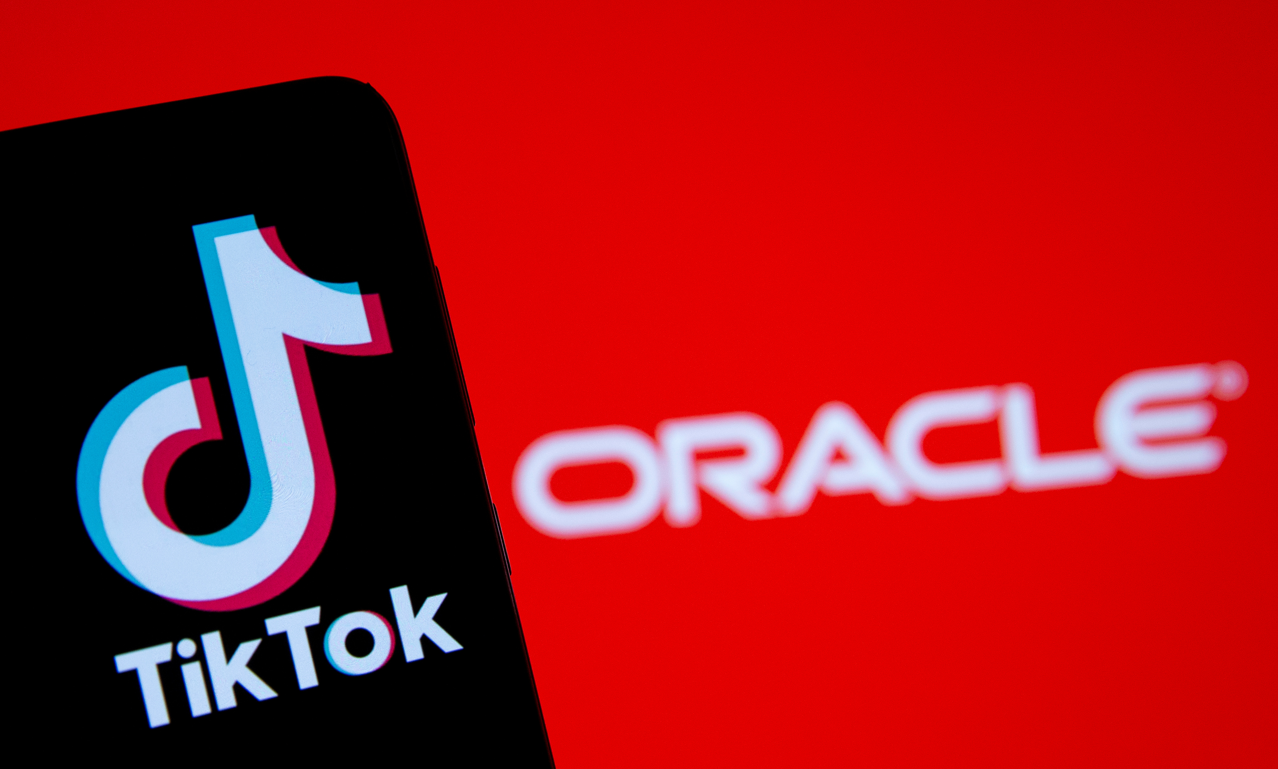 A smartphone with the Tik Tok logo is seen in front of a displayed Oracle logo in this illustration taken, Septemeber 14, 2020. REUTERS/Dado Ruvic/Illustration