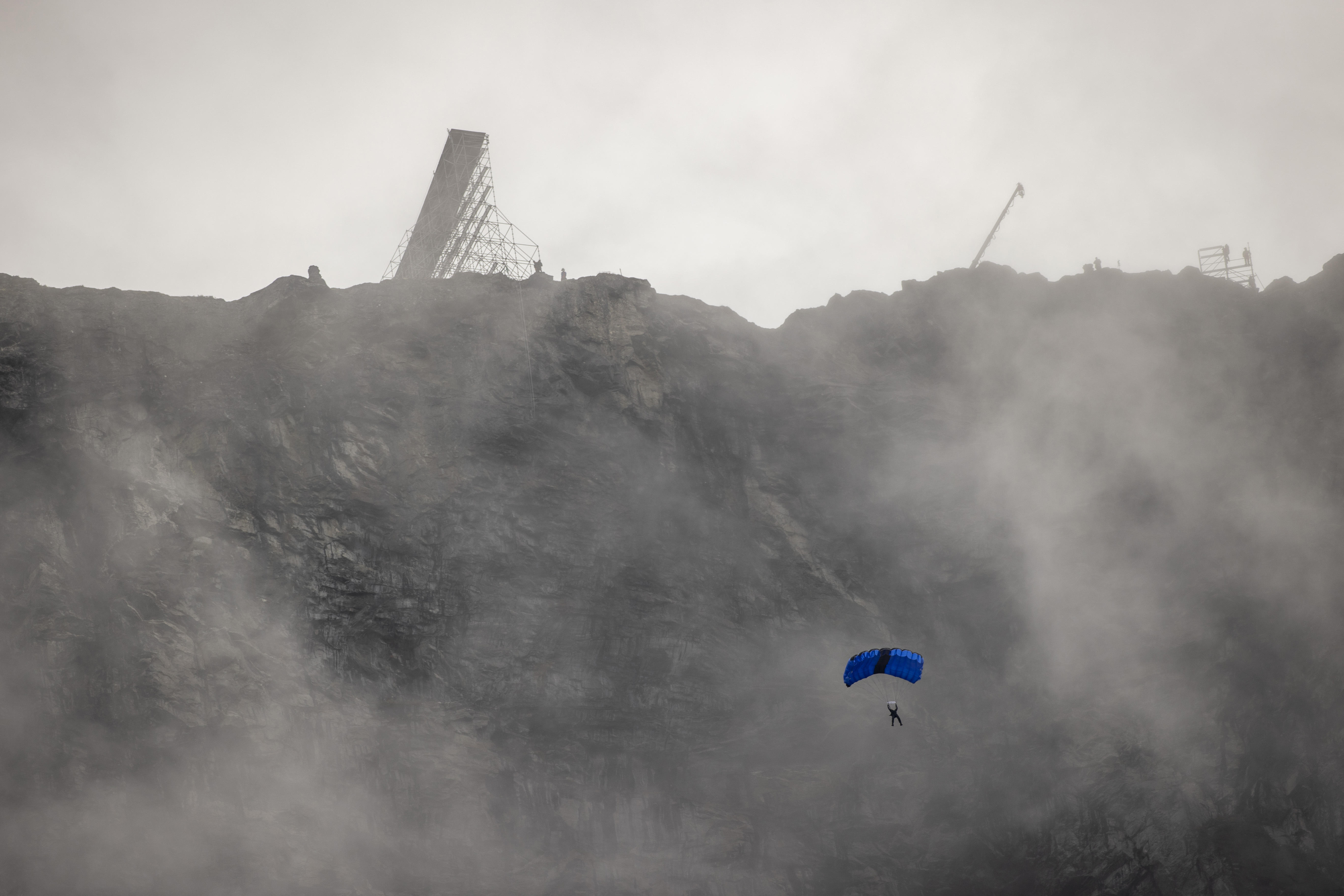 """Actor Tom Cruise during a parachute jump down the mountain Helsetkopen near to Hellesylt, Norway, during the recording of the next """"Mission: Impossible"""" film, Sunday Sept. 6, 2020.  After several days of waiting, the action hero completed four jumps with a motorcycle out of a huge ramp on the mountain top Helsetkopen near Hellesylt, Norway.  The bikes fell to the ground while Cruise landed by parachute down the steep mountainside. (Geir Olsen / NTB scanpix via AP)"""