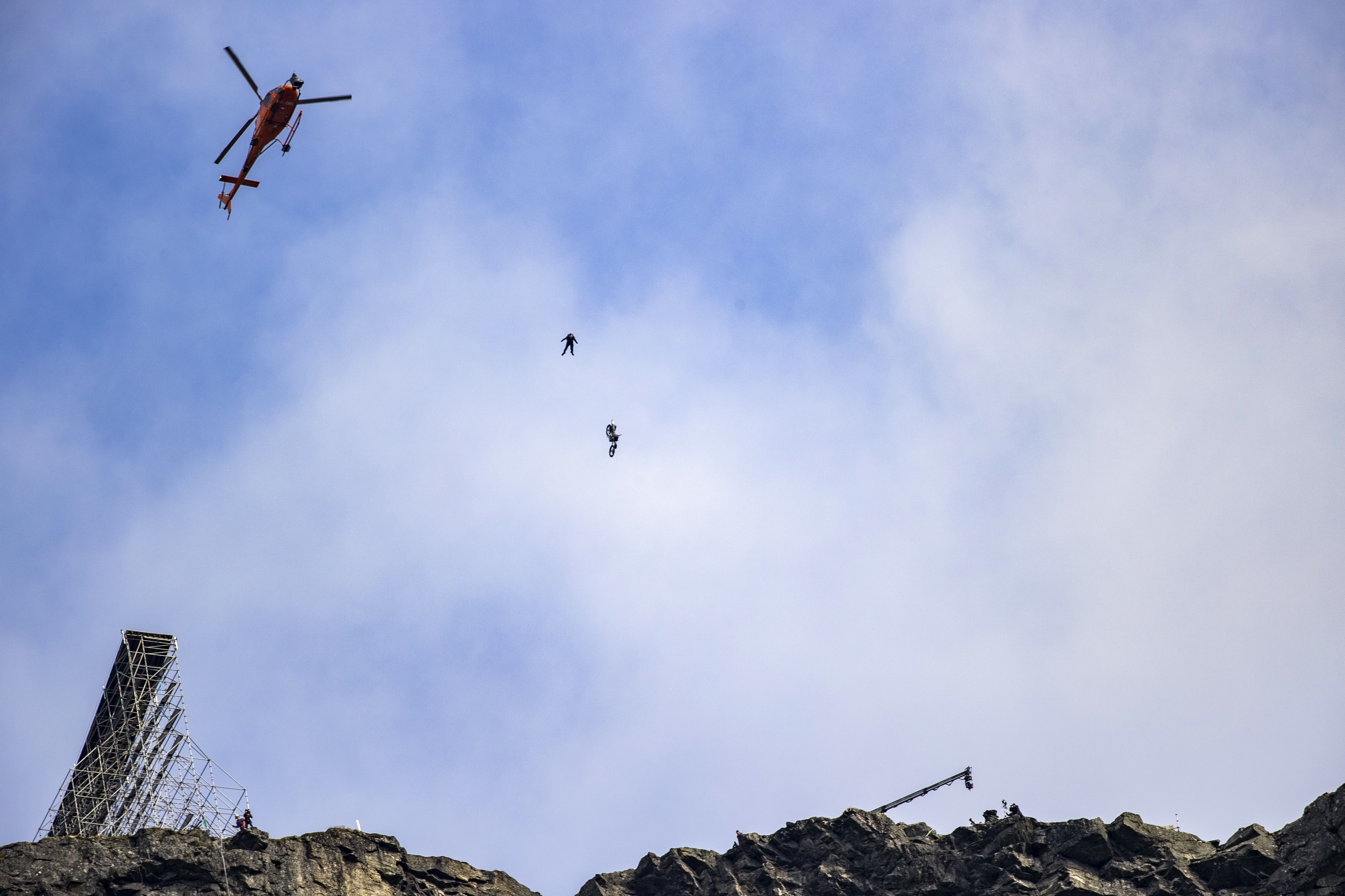 """Actor Tom Cruise in the air at Helsetkopen near to Hellesylt during the recording of the next """"Mission: Impossible"""" film, Sunday Sept. 6, 2020.  After several days of waiting, the action hero completed four jumps with a motorcycle out of a huge ramp on the mountain top Helsetkopen near Hellesylt, Norway.  The bikes fell to the ground while Cruise landed by parachute down the steep mountainside. (Geir Olsen / NTB scanpix via AP)"""