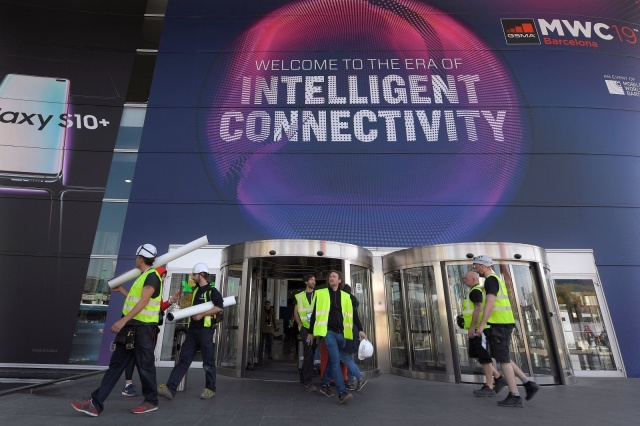 A group of MWC workers walk outside the 2019 Mobile World Congress venue few days before its opening in Barcelona on February 23 February, 2019. (Photo by LLUIS GENE / AFP)        (Photo credit should read LLUIS GENE/AFP/Getty Images)