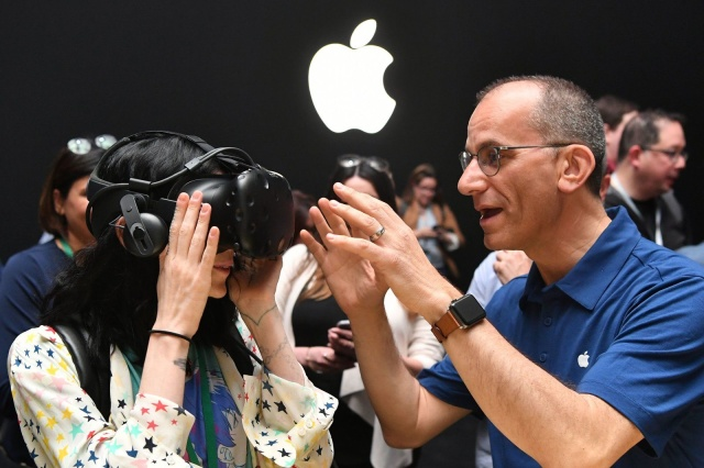 An Apple employee helps a member of the media try on an HTC Vive while testing the virtual reality capabilities of the new iMac during Apple's Worldwide Developers Conference in San Jose, California on June 5, 2017. / AFP PHOTO / Josh Edelson        (Photo credit should read JOSH EDELSON/AFP via Getty Images)