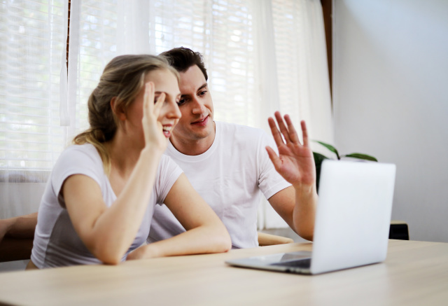 Happy couple lover talking and waving hand in a video conference on line with a laptop for contact frindship at home.