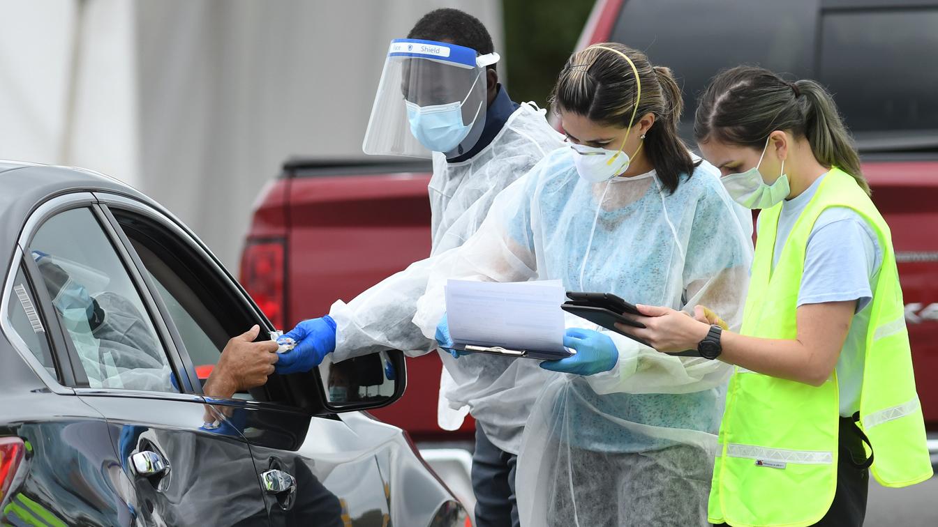 Οι εργαζόμενοι στον τομέα της υγειονομικής περίθαλψης χαιρετούν τους ανθρώπους καθώς φτάνουν σε έναν προσωρινό χώρο δοκιμών COVID-19 στο East Orange District Park την 1η Οκτωβρίου 2020 στο Ορλάντο της Φλόριντα. (Paul Hennessy / NurPhoto μέσω Getty Images)