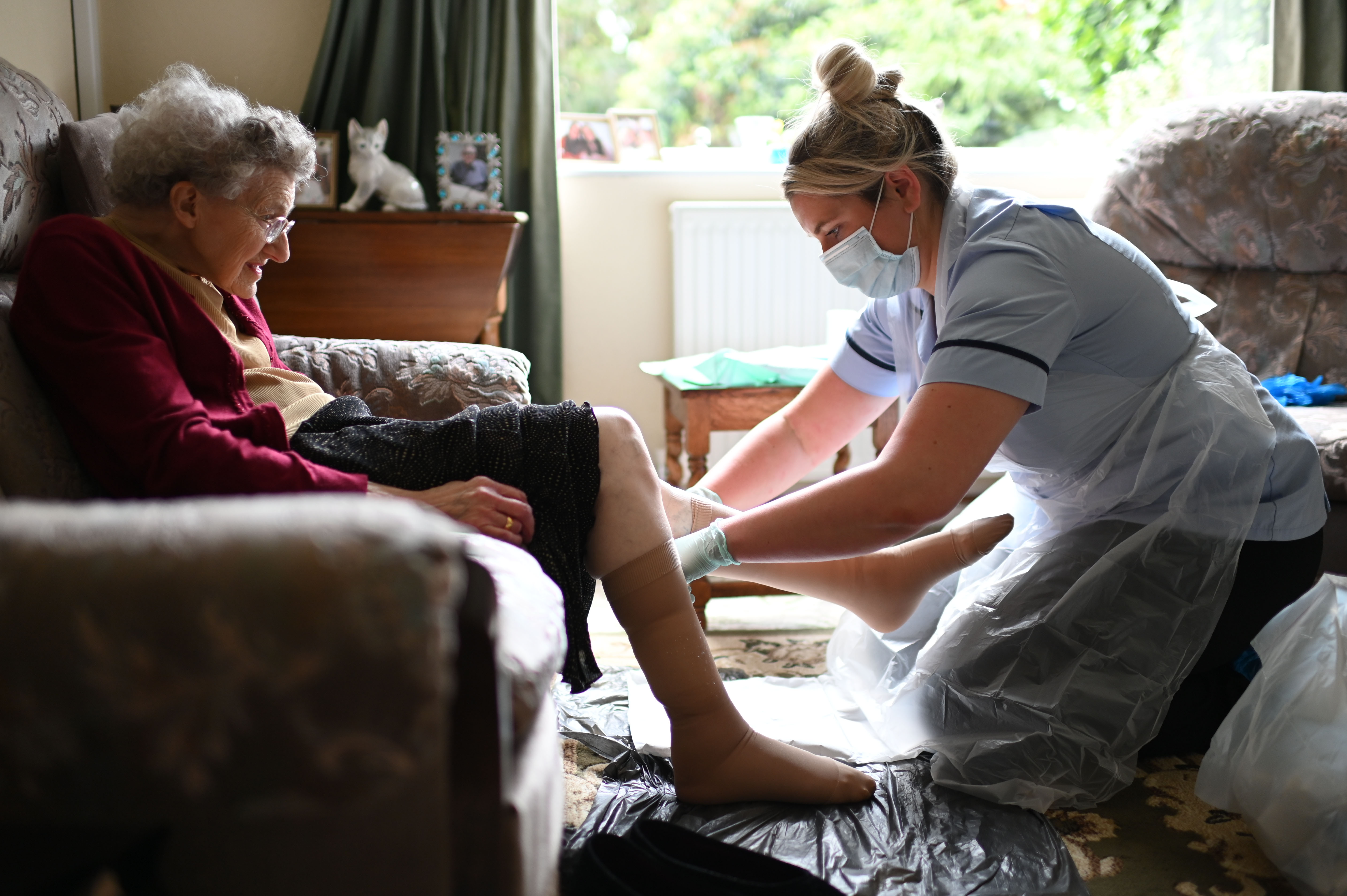 GRIMSBY, ENGLAND - JUNE 09: District nurse Rebecca McKenzie (R), wearing personal protective equipment (PPE) changes the dressings on the legs of 86-year-old Margaret Ashton (L) to treat her leg ulcers during a home visit on June 9, 2020 in Grimsby, northeast England. (Photo by Daniel Leal-Olivas - Pool/Getty Images)