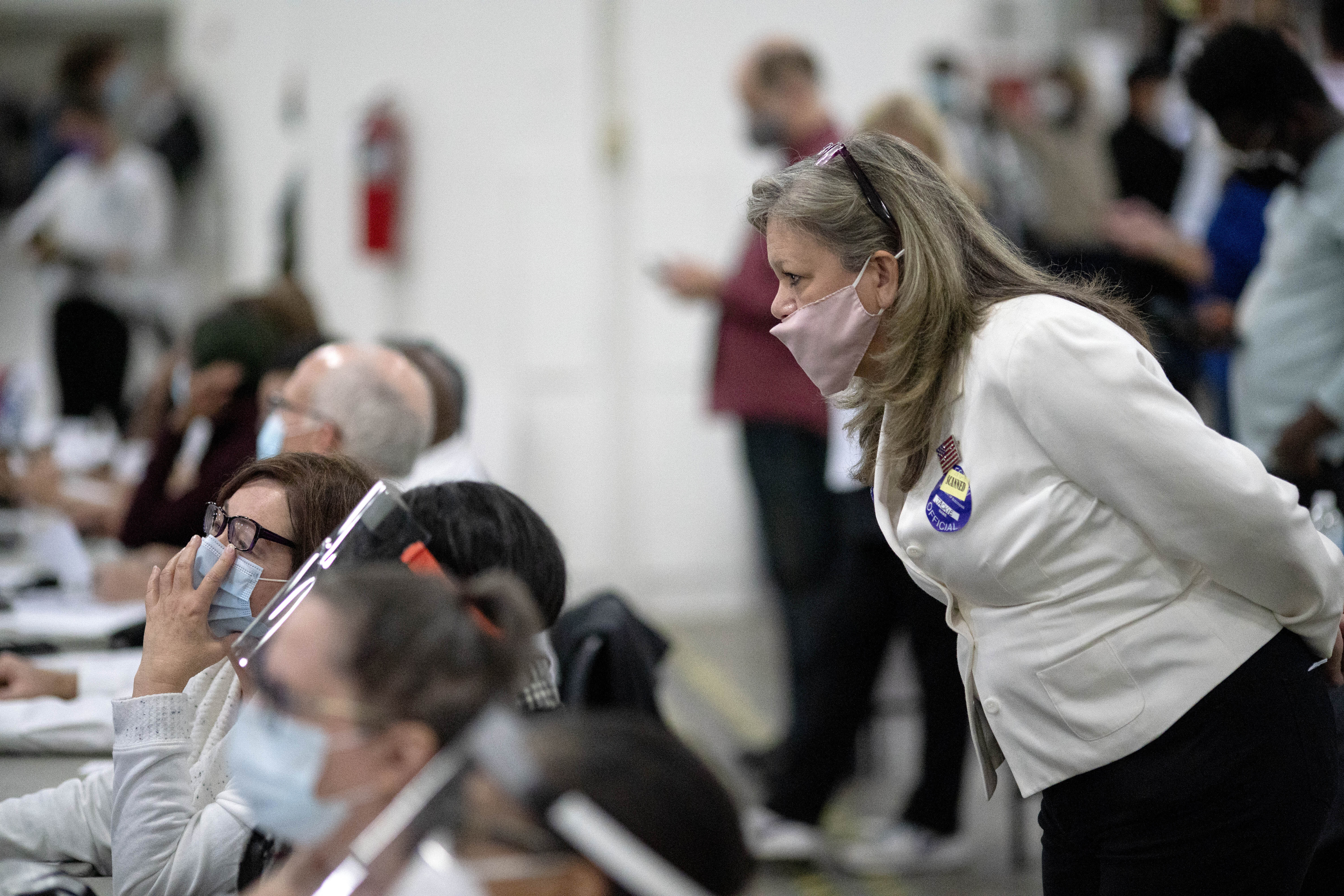 A Republican election challenger at right watches over election inspectors as they examine a ballot as votes are counted into the early morning hours Wednesday, Nov. 4, 2020 at the central counting board in Detroit. (David Goldman/AP)