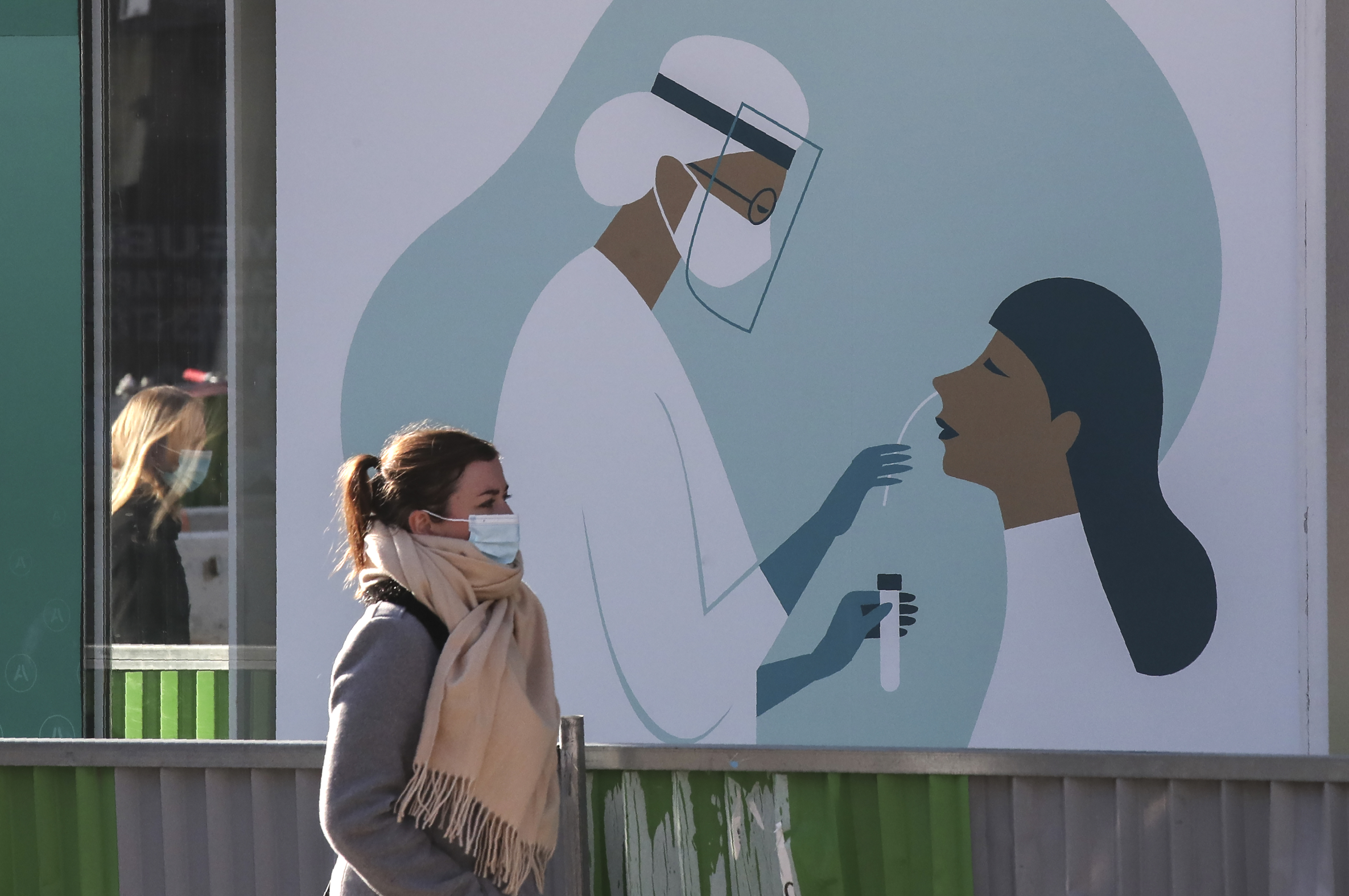 A woman walks past a billboard featuring a Covid test, displayed outside a pharmacy in Paris, Thursday, Nov. 5, 2020. In France, which is in a monthlong partial lockdown to stop fast-rising virus hospitalizations and deaths, the health minister may announce tighter measures at a weekly press conference later Thursday. (AP Photo Michel Euler)