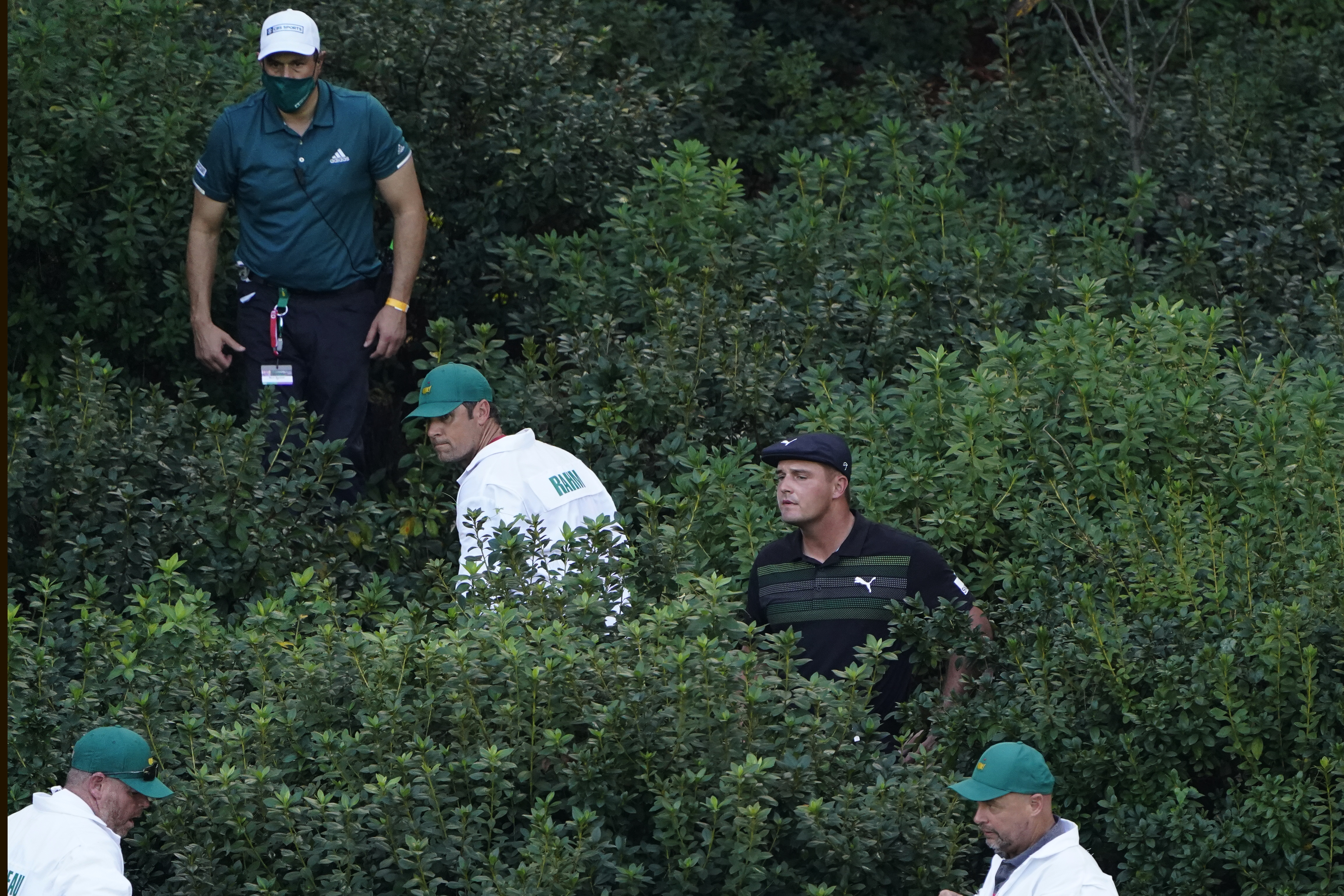 Bryson DeChambeau, caddies and officials look for his ball in the bushes on the 13th hole during the first round of the Masters golf tournament Thursday, Nov. 12, 2020, in Augusta, Ga. (AP Photo/Chris Carlson)