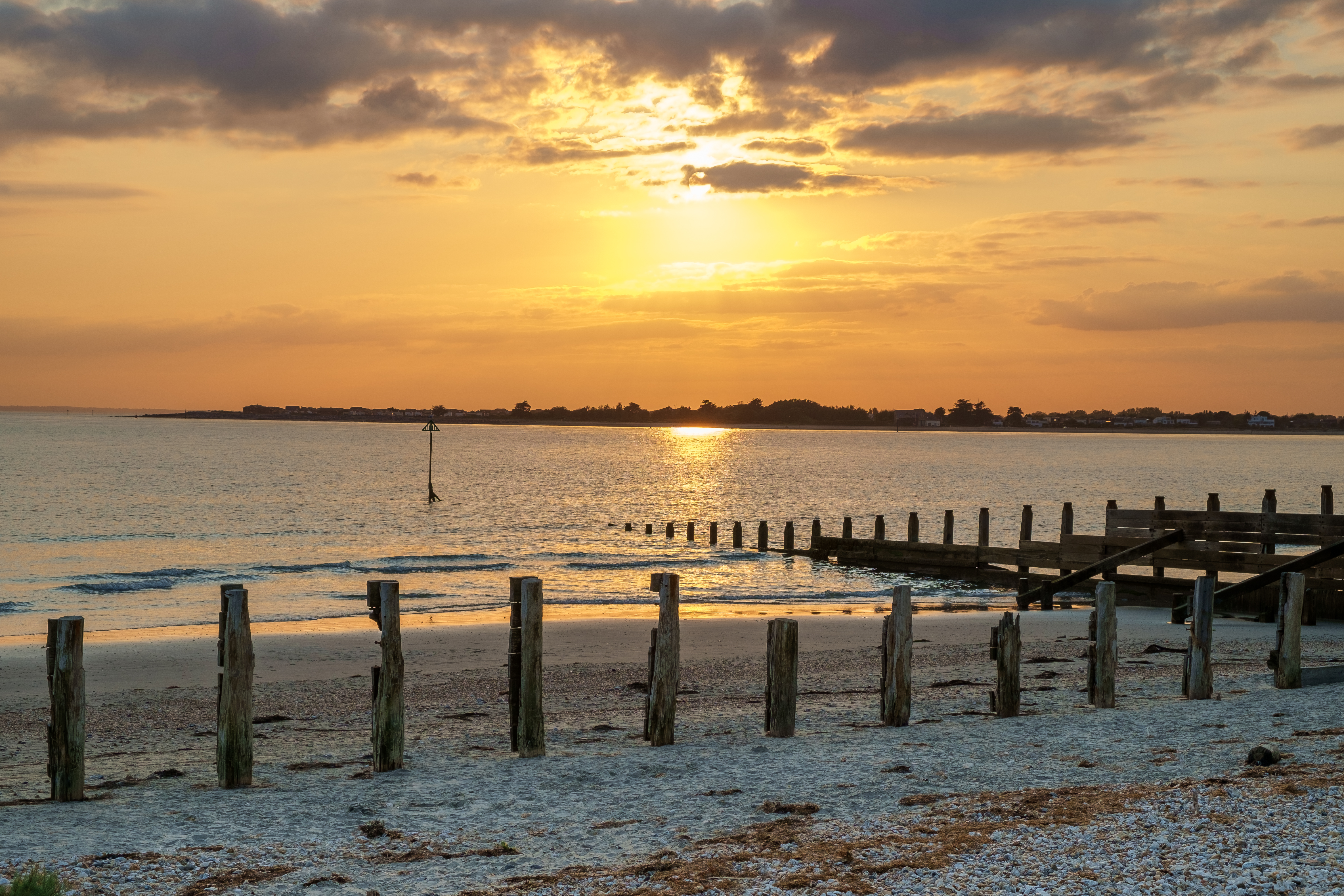 A wooden sea groyne stretches out into a calm sea in the golden light of the setting sun
