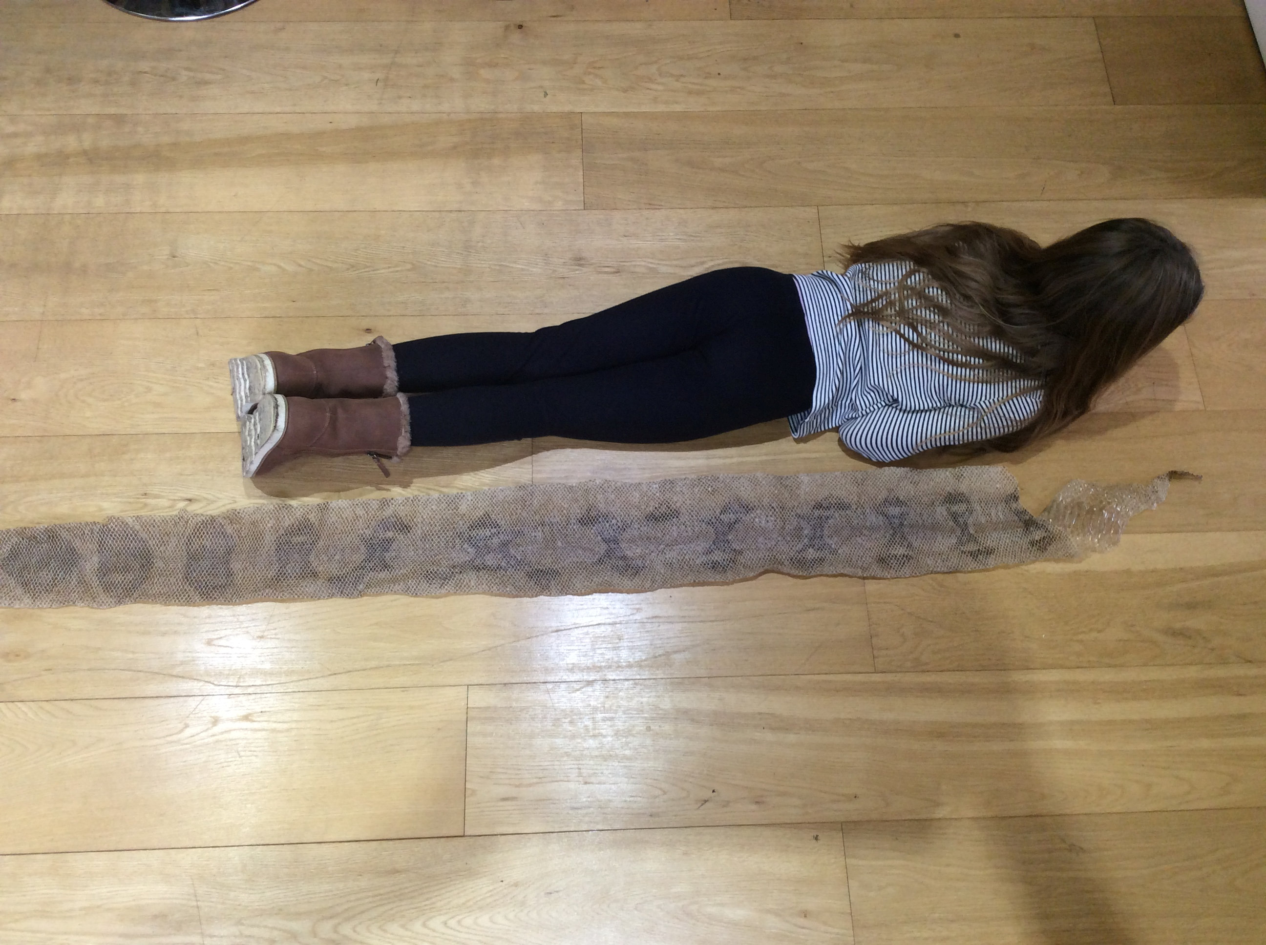 Amelia lying next to the gigantic snake skin. (SWNS)