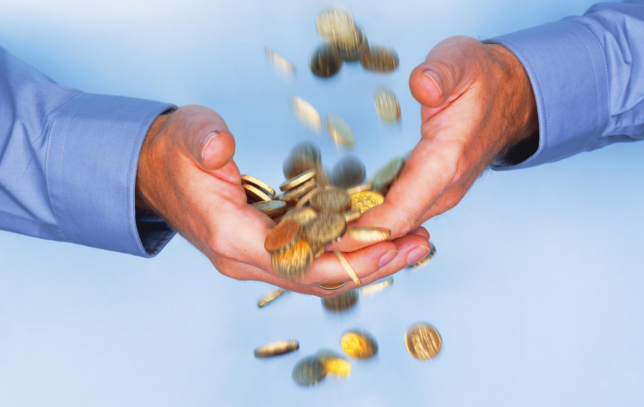 Gold coins falling through business man's hands