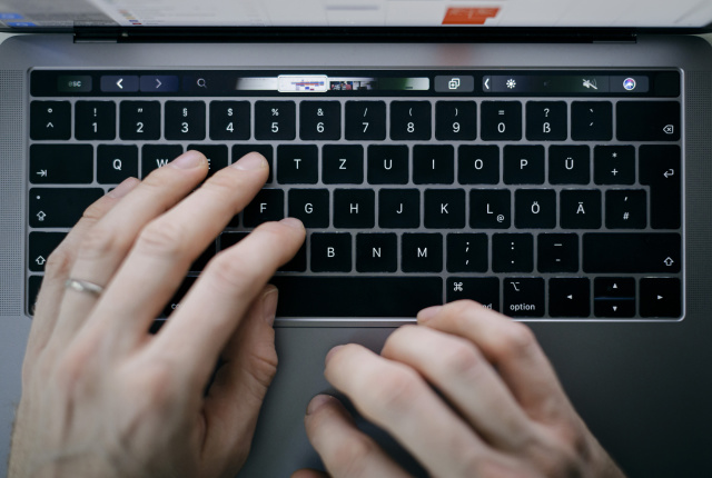 BERLIN, GERMANY - FEBRUARY 04: Symbol photo. A man is typing with his hands on a keyboard of a MacBook Pro on February 04, 2020 in Berlin, Germany. (Photo by Felix Zahn/Photothek via Getty Images)