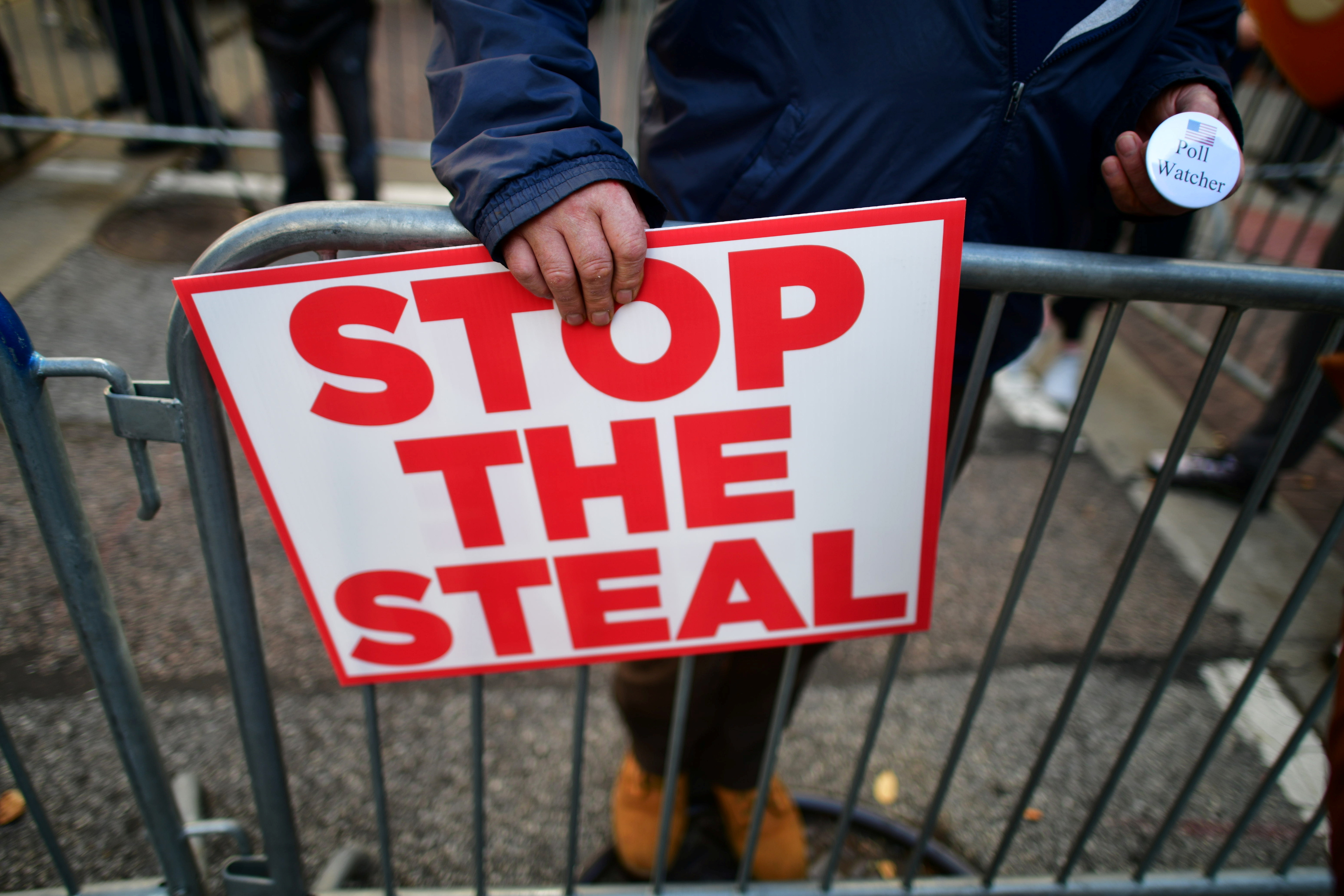 """A supporter of President Donald Trump holds a sign stating """"STOP THE STEAL"""" and a pin stating """"Poll Watcher""""in Philadelphia, Pennsylvania on November 6, 2020. (Mark Makela/Reuters)"""