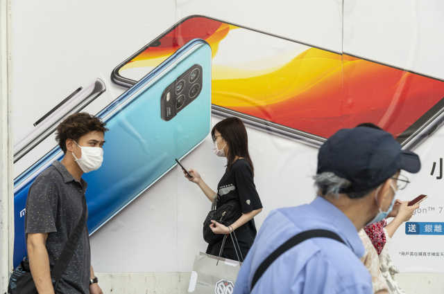 HONG KONG, CHINA - 2020/07/07: Commuters wearing face masks pass by a Xiaomi smartphone advertisement at its flagship store in Hong Kong. (Photo by Budrul Chukrut/SOPA Images/LightRocket via Getty Images)