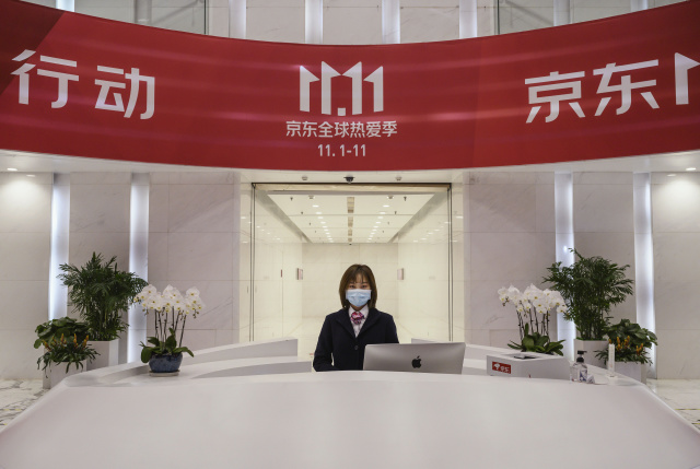 BEIJING, CHINA - NOVEMBER 11: A receptionist from Chinese e-commerce giant JD.com pose stands at her desk under banner for Singles Day in the lobby at the company's headquarters during an organized tour on November 11, 2020 in Beijing, China. The online shopping blitz, known as Singles Day or Double 11, is the world's largest retail event and comes as Chinese consumers are emerging from the COVID-19 pandemic. The revival of consumer consumption is expected to boost China's economy, which is already showing signs of post-pandemic recovery and providing a bright spot for global brands and retailers. Singles Day sales for China's biggest e-commerce giants like JD.com are on pace to break previous records, pulling in $56 billion U.S. in the first 30 minutes (when combined with three days of pre-event sales). (Photo by Kevin Frayer/Getty Images)